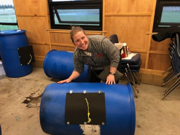 woman posing with an assembled compost tumbler