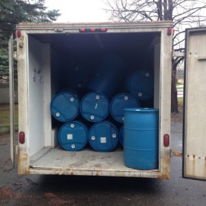 55 gallon blue barrels in a truck