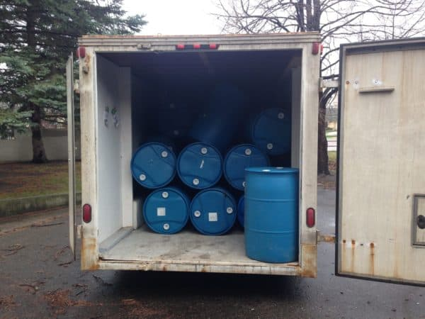 55 gallon blue barrels in a truck